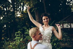 Groom holds bride in his arms Stock Photos