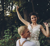 Groom holds bride in his arms Stock Photography