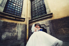 Groom holds bride on his arms standing under big windows Stock Photo