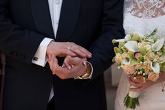 Groom holds bride's arm delicately Stock Images