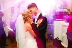 Groom holds bride`s face kissing her in the restaurant hall Royalty Free Stock Images