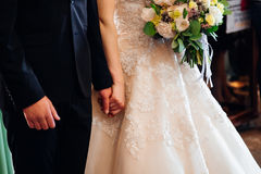 Groom holds bride& x27;s hand behind her luxurious dress royalty free stock images
