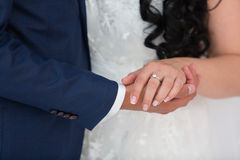 Groom holds the bride's hand. The groom holds a hand of the bride outdoors Royalty Free Stock Photos