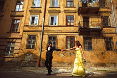 Groom holds bride's hand and pulls her along an old house Stock Photo