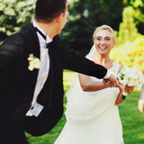 Groom holds bride's hand while they run across the park.  Stock Photography