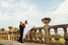 Groom holds bride& x27;s hand while she sits on ol stone handrails.  Stock Image