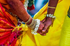 Groom holds bride`s hand Stock Images