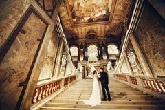Groom holds bride`s hand standing on the stairs in painted hall. Of a theatre in Vienna Stock Image