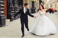 Groom holds bride`s hand tightly while they run along old buildi Stock Image