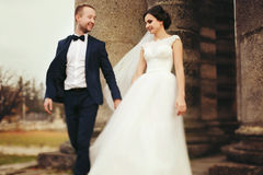 Groom holds bride`s hand walking with her from the ruined cathed Stock Photos