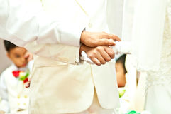 Groom holds bride's hand in wedding day Stock Photos
