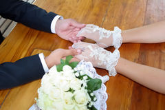 The groom holds the bride's hands at the table Royalty Free Stock Images