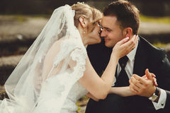 Groom holds bride's hands tenderly while she kisses him Stock Image