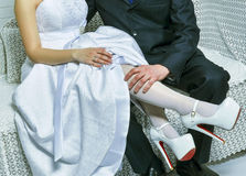 Groom holds bride's leg in white Royalty Free Stock Photography