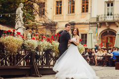 Groom holds bride`s waist posing behind a wooden street cafe.  stock photos