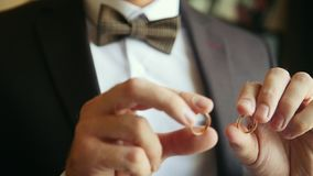 Groom holds golden wedding rings in hands - wedding concept stock video footage