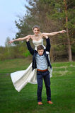 Groom holds his bride in arms and smiles of happiness Stock Photos