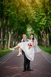 Groom holds his bride in arms and smiles of happiness in summer park Royalty Free Stock Photography