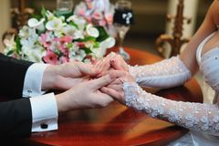Groom holds his bride's hand Stock Photo