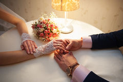 Groom holds his bride's hand at the table Royalty Free Stock Image