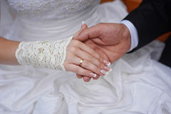 Groom holds his bride's hand with wedding ring Stock Photos