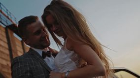 Groom holds his bride's waist on a background of a dam stock video