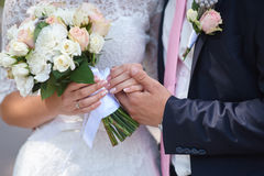 Groom holds his brides hand and a wedding bouquet Royalty Free Stock Image