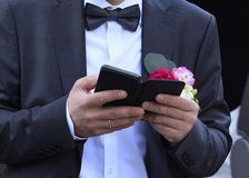 The groom holds phone in hand stock image