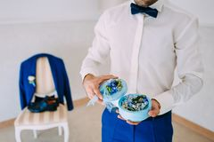 Groom holds a round box with Wedding rings with blue flowers. Artwork. Soft focus Royalty Free Stock Photos