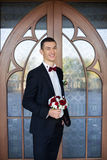 The groom holds a tie and smiles.Portrait of the groom in the park on their wedding day.Rich groom on their wedding day. The groom holds a tie and smiles Stock Photo