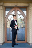 The groom holds a tie and smiles.Portrait of the groom in the park on their wedding day.Rich groom on their wedding day. The groom holds a tie and smiles Stock Photography