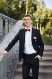 The groom holds a tie and smiles.Portrait of the groom in the park on their wedding day.Rich groom on their wedding day. The groom holds a tie and smiles Stock Image