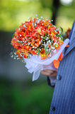 Groom holds a wedding bouquet Royalty Free Stock Image