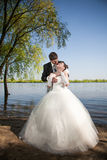 Groom hugging from back bride on white dress Royalty Free Stock Images