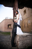 Groom hugging beautiful bride standing on high parapet Stock Photography