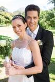 Groom hugging bride from behind in park Royalty Free Stock Photo
