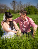 Groom hugging bride on big field at sunny day Royalty Free Stock Photography