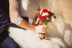 Groom hugging bride holding wedding bouquet Royalty Free Stock Image