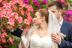 Groom hugging bride smelling flowers at park Royalty Free Stock Photos