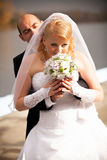 Groom hugging bride that is smelling flowers Stock Photography