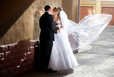 Groom hugging bride while wind lifting veil Stock Photo