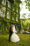 The groom is hugging his bride opposite the building with ivy. Stock Image