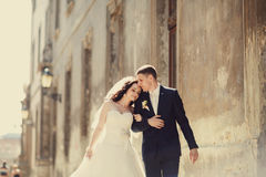 Groom huging kissing bride near wall outdoors Lviv Royalty Free Stock Photography