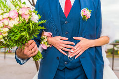 Groom hugs bride with bouquet of flowers. stock image