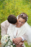 Groom hugs his bride with roses and kisses neck Royalty Free Stock Photo
