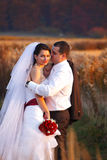 Groom hugs a smiling bride holding a jacket over his shoulder Stock Images