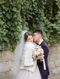 Groom hugs tender bride in white fur coat under the wall Stock Photography