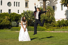 Groom jumping. Next to his bride Stock Photography