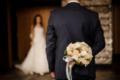 Groom keeping behind a bouquet of roses waiting for bride. Groom in a stylish suit keeping behind a bouquet of roses waiting for his charming brunette bride stock photos