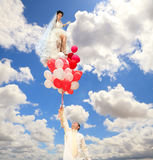 Groom keeps a  bride on  balloons. A groom keeps a  bride on the red and white balloons against cloudy sky Royalty Free Stock Photography